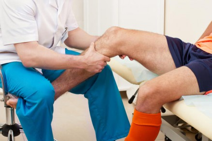 Doctor examining a patient complaining of knee pain.