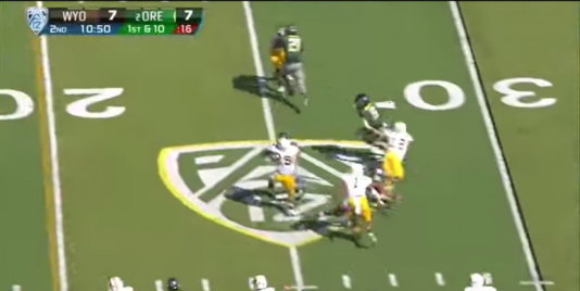 Grasu's block disrupts the defender's timing and throws him off course, causing him to whiff while trying to tackle running back Byron Marshall.