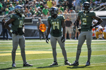 Reggie Daniels (8) with Tyree Robinson (2) and former Duck Ifo Ekpre-Olomu (14)
