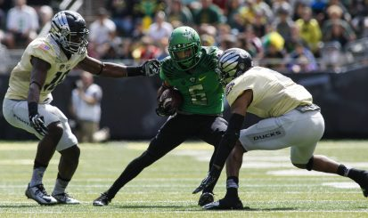Nelson makes a move on two defenders during the Oregon spring game.