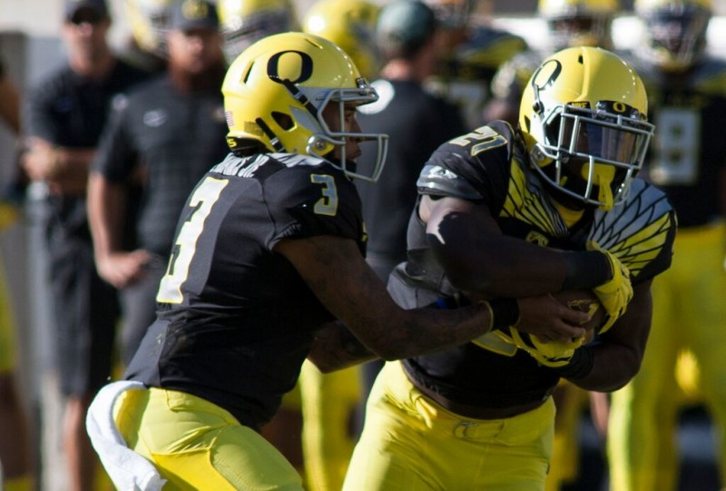 Vernon Adams hands off to Royce Freeman.