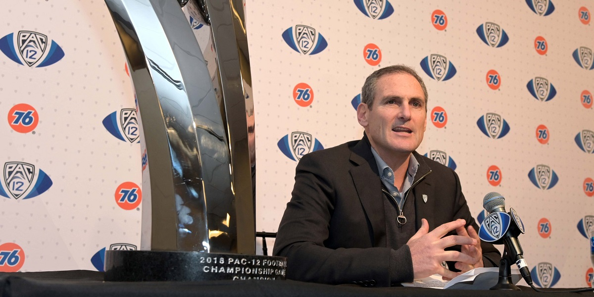 Image of Larry Scott sitting next to Pac-12 Championship trophy.